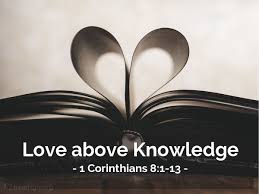 "The black and white image of an open book with pages on either side turned into middle to reveal a heart shape. The words ""Love above Knowledge - 1 Corinthians 8: 1-13"" are written below the book."