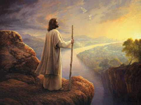 Image of Jesus in white robes with a staff standing on a cliff. He is in the shadow facing the rising sun.