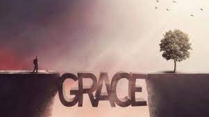 """Image of two cliffs with a bridge shaped in the word """"GRACE"""" between the two. A single person in the shadows is on one side and a single tree drenched in light is on the other side."""