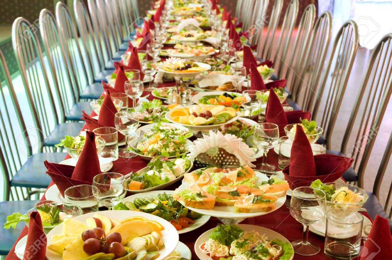 An image of a food banquet with many empty chairs. The food is primarily colorful fruits and vegetables with red napkins in the shape of birds on each plate.