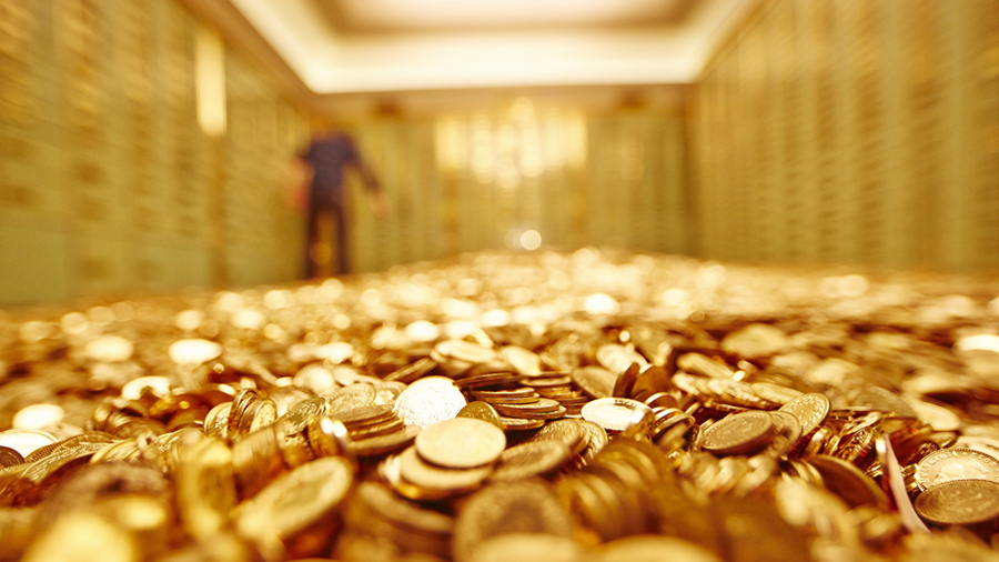 An image of a man standing on a pile of gold coins in a vault.