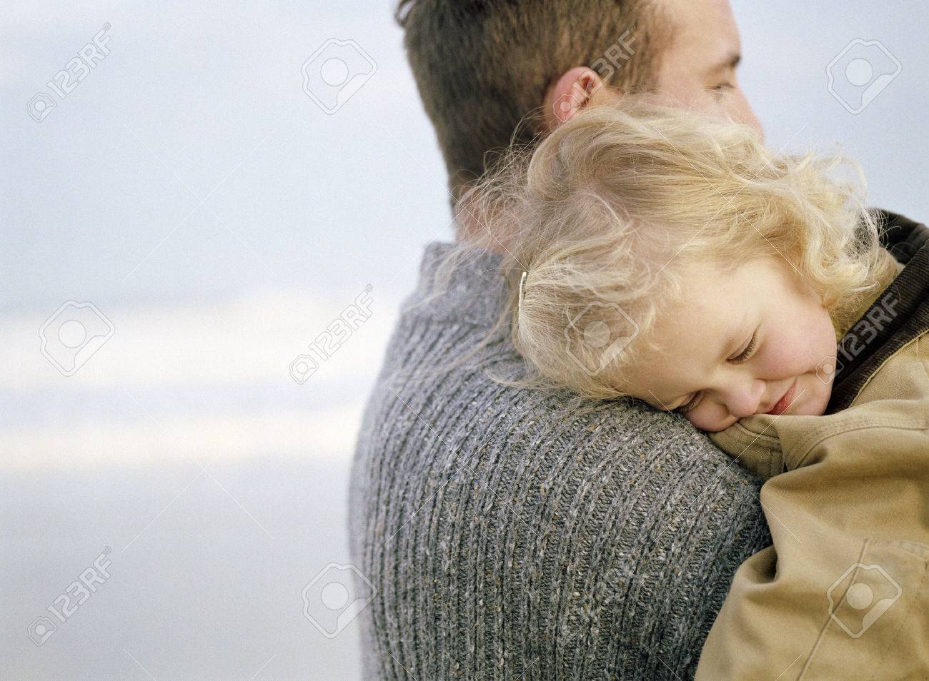 Little girl being carried on the beach by an adult male apparent figure. She has her head on his shoulder.