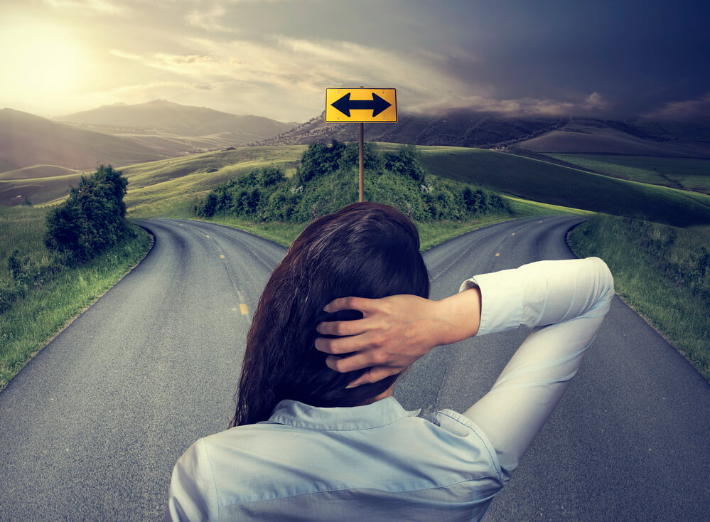 Image of a woman trying to decide which road to go down. One side is bright and sunlit. The other is dark and shadowy.