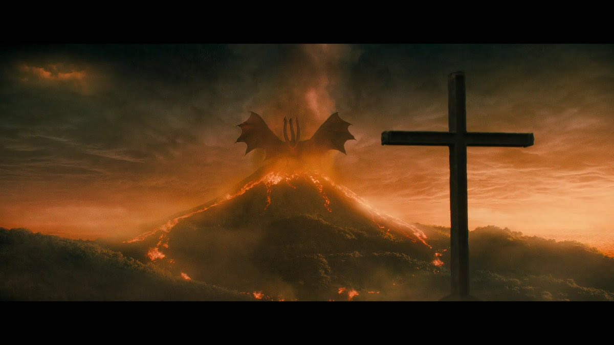 An image of a multi headed beast / dragon sitting on a volcano with a cross in the foreground.