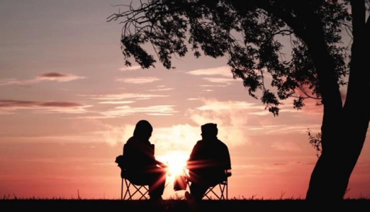 An image of the silhouette of two people sitting and talking calmly in front of an orange hued sunset. There is a tree in the foreground.