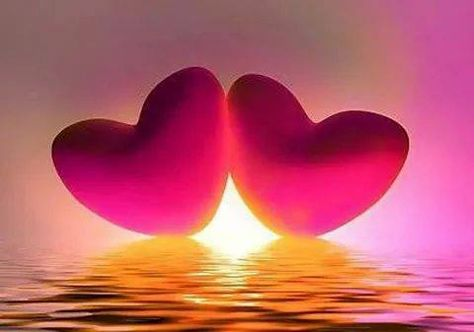 Picture of two hearts in front of a sunrise over the water.